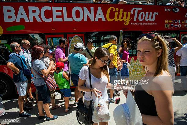 Tourists wait for a tourist tour bus on July 11 2014 in Barcelona Spain As traders of 'La Boqueria' complain about tour groups getting in the way of...