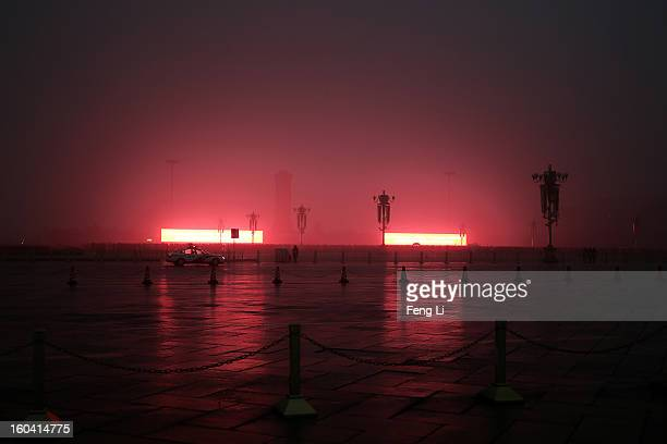 Tourists wait for the flagraising ceremony on the Tiananmen Square during severe pollution on January 31 2013 in Beijing China Heavy smog that has...