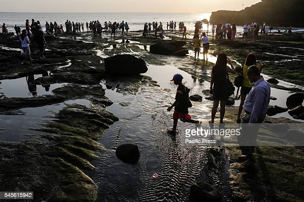 Tourists wait for the sunset in the area of Tanah Lot Temple during the third day of Eid holiday. This iconic Balinese Hindu Temple was built on the...