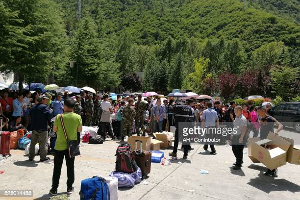 Tourists wait to be evacuated after an earthquake in Jiuzhaigou in China's southwestern Sichuan province on August 9 2017 At least 13 people were...