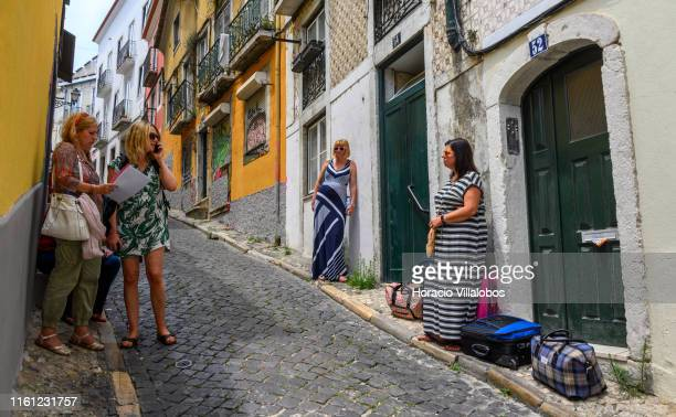 Tourists wait to be let into their rented apartment in Calçada Salvador Correia de Sa Santa Catarina historical neighborhood on July 10 2019 in...