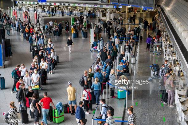 Tourists wait to check in for a TUIfly flight to Mallorca at Frankfurt Airport on the first day that package tours are resuming since March during...
