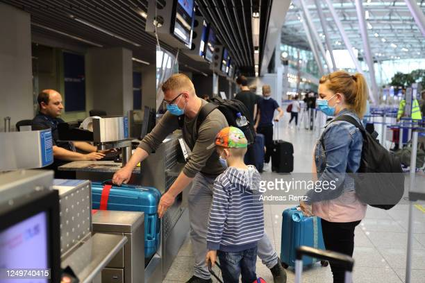 Tourists wait to check in for TUIfly flight X3 2312 the first package tour flight to Mallorca since March at Dusseldorf Airport during the...