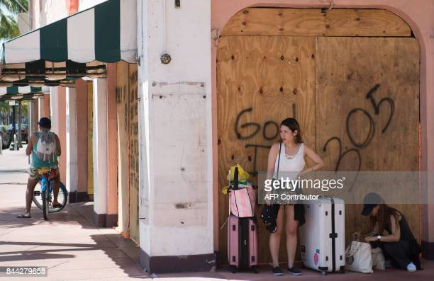 Tourists wait with their luggage as they prepare to leave in advance of Hurricane Irma during a mandatory evacuation in Miami Beach Florida September...