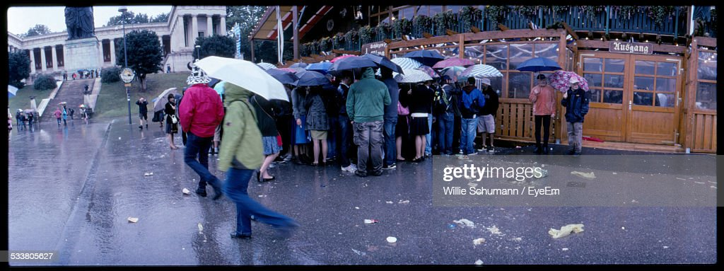 Tourists Waiting In Line And Holding Umbrellas : Foto stock