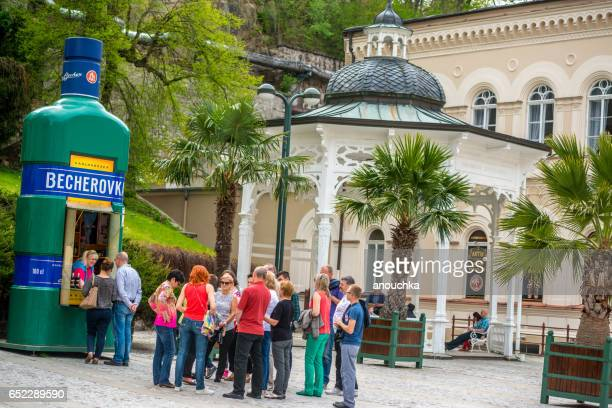 tourists waiting in line to buy becherovka, famous drink in karlovy vary - karlovy vary stock pictures, royalty-free photos & images