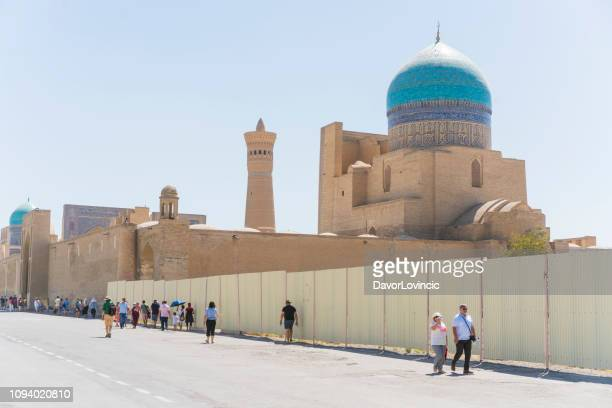 tourists waling on road from ark fortress to the kalon  mosque and miri arab medressah in bukhaea, uzbekistan. - unesco stock pictures, royalty-free photos & images