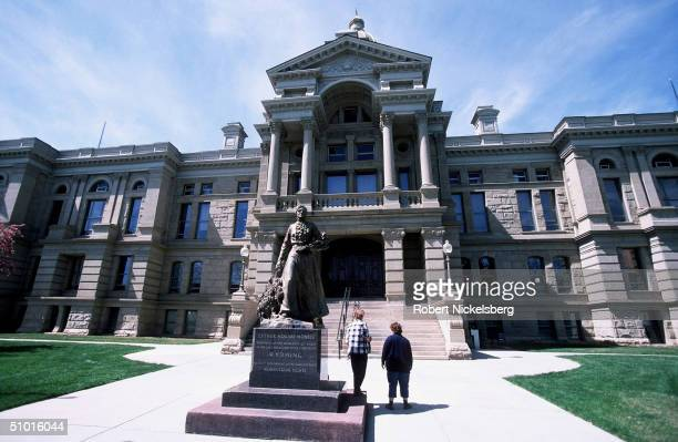 Tourists walk about the capital building May 2 2004 in Cheyenne Wyoming The statue is of Esther Hobart Morris who was the proponent of the...