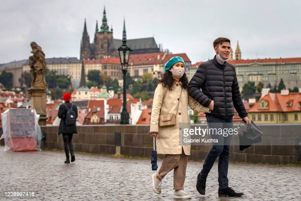 Tourists walk across medieval Charles Bridge on October 10, 2020 in Prague, Czech Republic. After relaxing almost all restrictive measures in the...