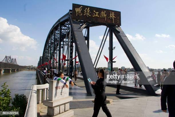Tourists walk across the Broken Bridge on the Yalu river in Dandong, China near the North Korean border.