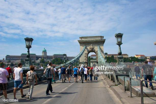 Tourists walk across the Széchenyi Chain Bridge spanning across the River Danube in Budapest, Hungary, 21 August 2015. Photo: Ursula Dueren/dpa |...