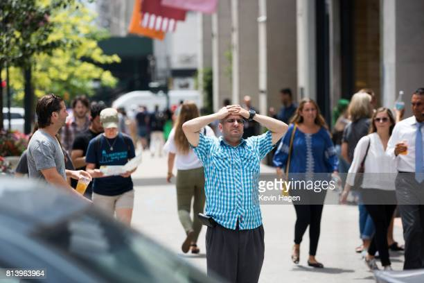 Tourists walk along 6th Avenue in Manhattan on July 13 2017 in New York City New Yorkers are experiencing highthannormal temperatures as the the...