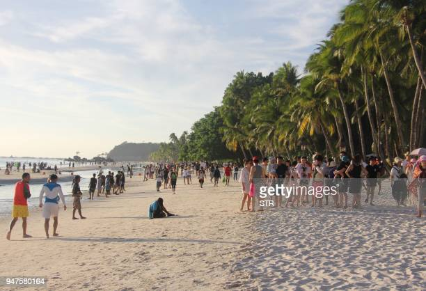 Tourists walk along a beach in Boracay Malay town in central Philippines on April 17 ahead of its closure The Philippines is set to deploy hundreds...