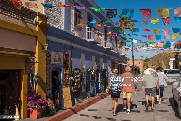 tourists walk along a flag draped street in todos santos, mexico. - todos santos mexico fotografías e imágenes de stock