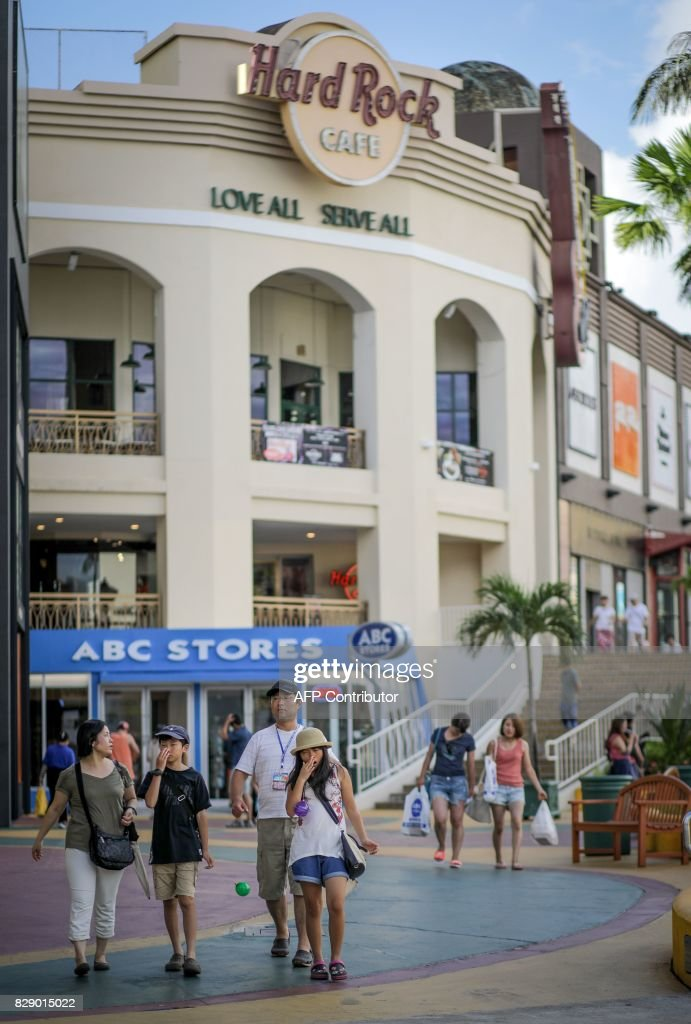 Tourists walk along a shopping area in the city of Tamuning on the island of Guam on August 10, 2017. Guam's governor on August 10 said the US territory was 'well-equipped' to handle any North Korean strike thanks to robust infrastructure that had survived earthquakes and typhoons, after Pyongyang released a detailed plan to launch missiles towards the island. / AFP PHOTO / Robert TENORIO
