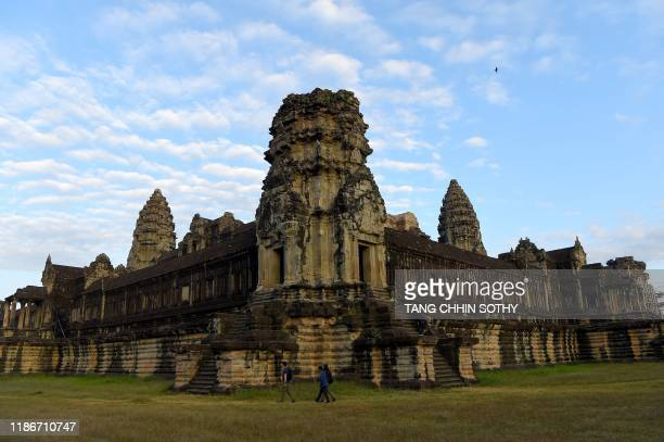 Tourists walk along the Angkor Wat temple in Siem Reap province on December 6, 2019.