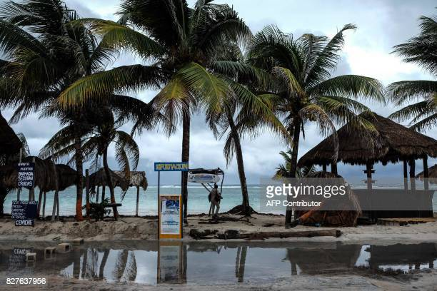 Tourists walk along the beach in Mahahual Quintana Roo State on August 8 2017 after tropical storm Franklin made landfall on Mexico's Yucatan...