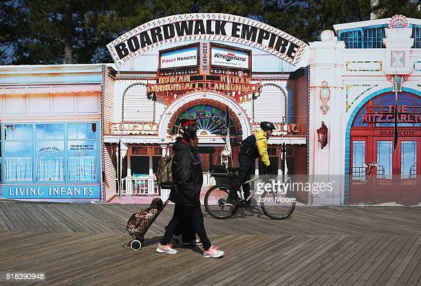 Tourists walk along the boardwalk on March 30 2016 in Atlantic City New Jersey The Atlantic City municipality is due to run out of funds on April 8...