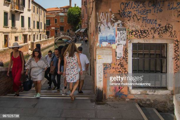 Tourists walk along the canal De La Toletta where there are graffiti and tags on the walls on the way that connects Accademia bridge to Railway...