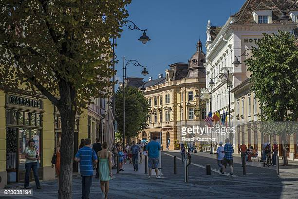 Tourists walk along the charming streets of Sibiu, Romania in morning light.
