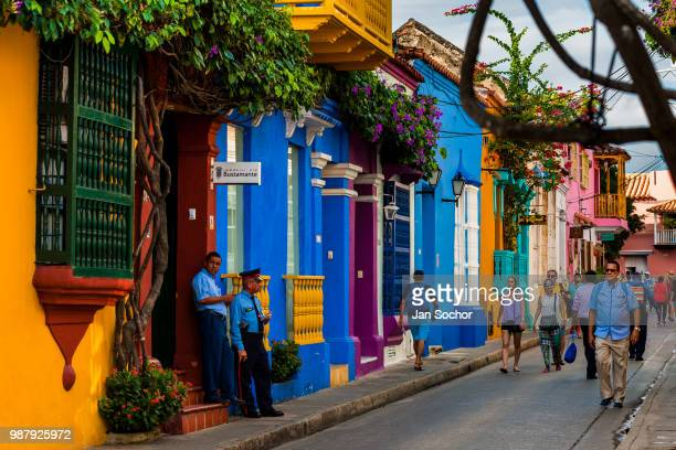Tourists walk along the colorfully painted colonial houses in the street located within the historical walled city on December 12 2017 in Cartagena...