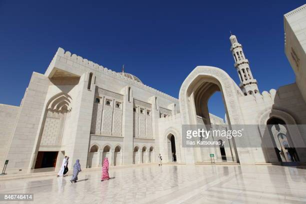 tourists walk along the exterior courtyard of the sultan qaboos grand mosque, in muscat, oman - arabian peninsula stock pictures, royalty-free photos & images