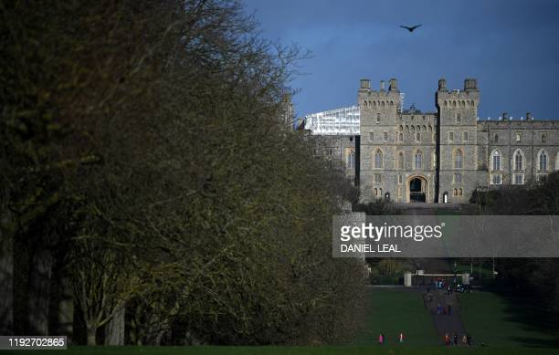 Tourists walk along the Long Walk at Windsor Castle in Windsor, west of London on January 9, 2020. - Britain's Prince Harry and his wife Meghan...