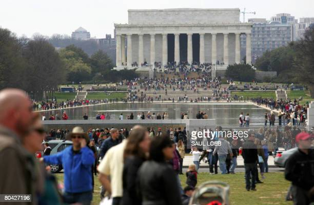 Tourists walk along the National Mall near the Lincoln Memorial and Reflecting Pool in Washington, DC, on March 29, 2008. AFP PHOTO/SAUL LOEB