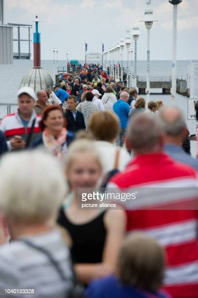 Tourists walk along the pier on Usedom island in the Baltic Sea spa town of Zinnowitz, Germany, 02 August 2016. Photo: STEFANSAUER/ZB | usage...