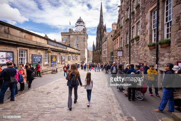 tourists walk along the royal mile near edinburgh castle - edinburgh castle stock pictures, royalty-free photos & images