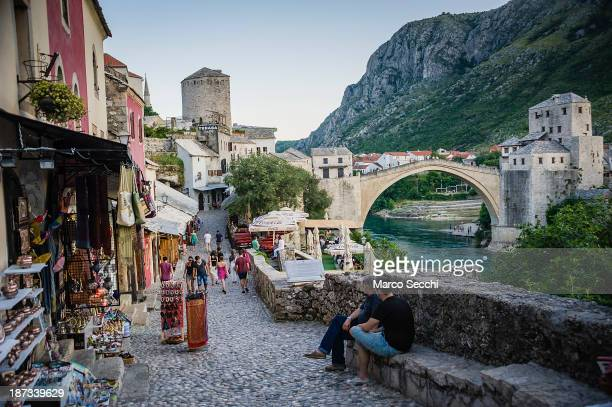 Tourists walk along the street leading to the Old Bridge on June 26, 2013 in Mostar, Bosnia and Herzegovina. The Siege of Mostar began in 1992 during...