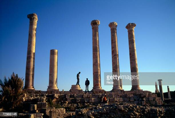 Tourists walk among Corinthian columns in the Roman ruins of the Temple of Liber Pater which flourished in the time of the ancient region of...