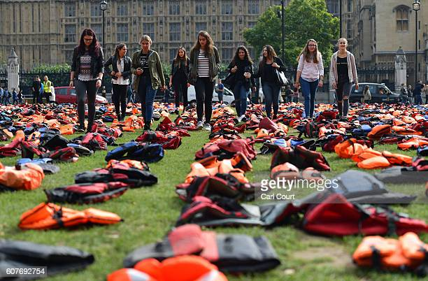 Tourists walk among lifejackets that have been used by refugees to cross the sea to Europe as they are laid out in Parliament Square on September 19...