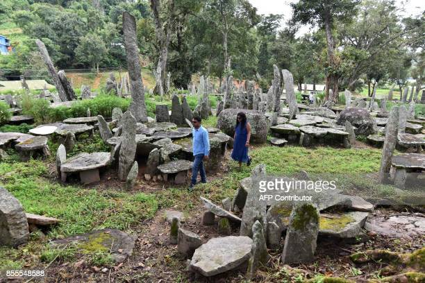 Tourists walk amongts the monoliths in Nartiang village in Meghalaya northeastern Indian state on September 29 2017 / AFP PHOTO / Biju BORO