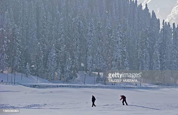Tourists walk and ski through a snowcovered landscape in Gulmarg situated about 55 kms north of Srinagar on January 13 2012 Gulmarg is the main ski...