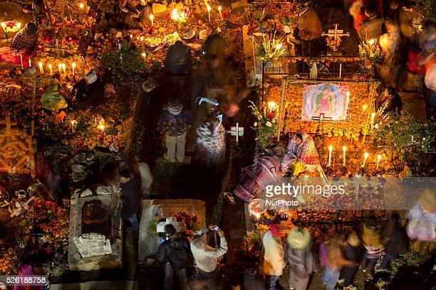 Tourists walk and take pictures during the celebration of the Day of the Dead while locals watch their dead in the cemetery of Janitzio Michoacan on...