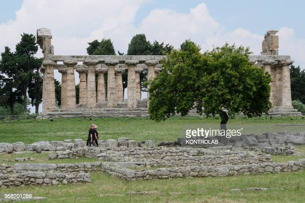 Tourists walk and take pictures near Athena Temple inside archaeological park of Paestum near Salerno southern Italy