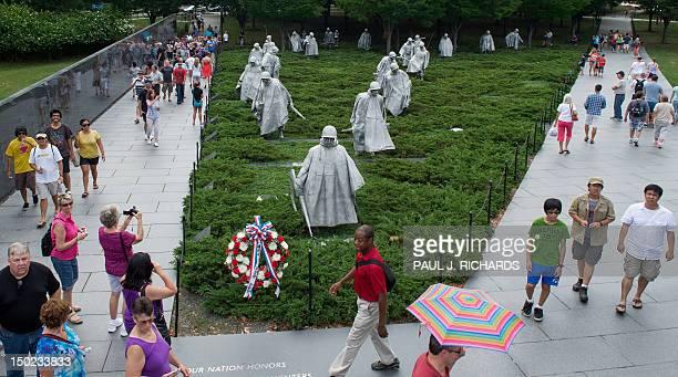 Tourists walk around the Korean War Memorial August 11 2012 in Washington DC AFP PHOTO/Paul J Richards