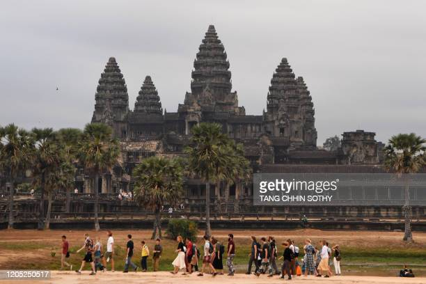 Tourists walk as they visit Angkor Wat temple in Siem Reap province on March 5, 2020. - The deadly COVID-19 novel coronavirus epidemic will cost...