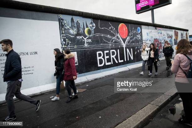 Tourists walk at a former section of the Berlin Wall called the East Side Gallery on the first day of events celebrating the 30th anniversary of the...