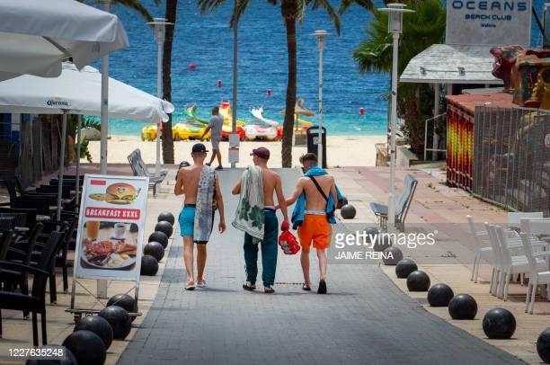 Tourists walk at General Garcia Ruiz street in Magaluf, Calvia, in Spain's Balearic island of Majorca on July 16, 2020. - Regional authorities on...