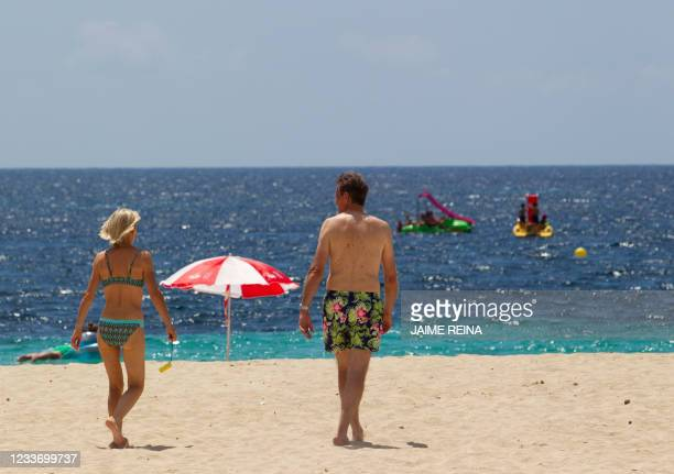 Tourists walk at Magaluf Beach in Calvia, on the Balearic Island of Mallorca, on June 28, 2021. - British holidaymakers heading to the Balearic...