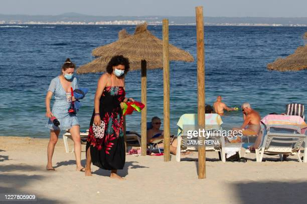 Tourists walk at Palmanova Beach on the Island of Mallorca on July 27, 2020. - Tour operator TUI has cancelled all British holidays to mainland Spain...