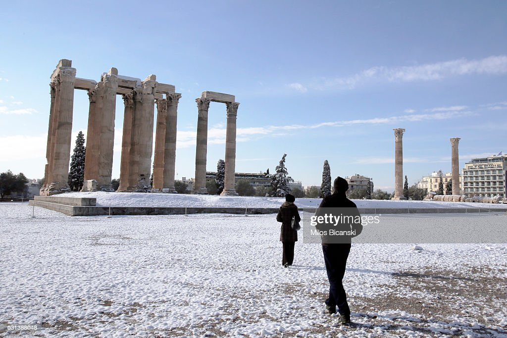 Tourists walk at the archaeological site of the ancient Temple of Zeus which is covered with snow on January 10, 2017 in Athens, Greece.