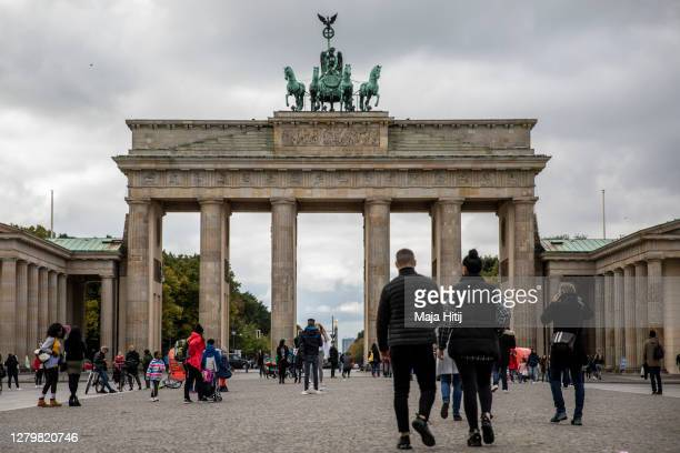 Tourists walk at the Brandenburg Gate on October 12, 2020 in Berlin, Germany. Berlin and several cities have already breached limit of infection...