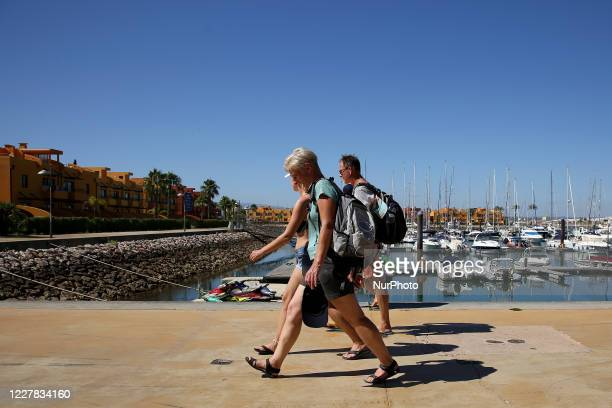 Tourists walk at the Marina in Portimao, Algarve region, Portugal on July 29, 2020. Portuguese President Marcelo Rebelo de Sousa has promised to...