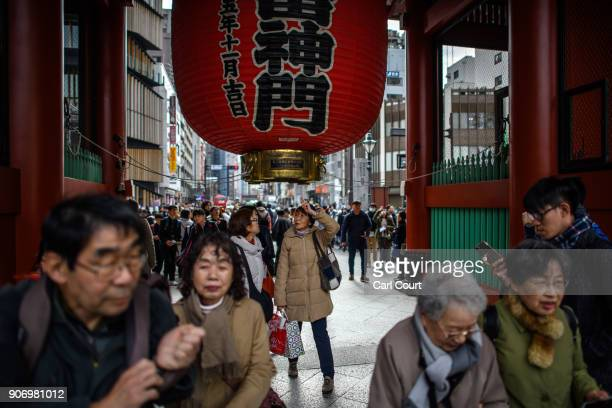 Tourists walk beneath a huge lantern in Sensoji buddhist temple on January 19 2018 in Tokyo Japan Sensoji is Tokyo's oldest temple dating back to 628...
