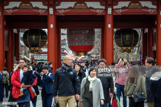 Tourists walk beneath huge lanterns in Sensoji buddhist temple on January 19 2018 in Tokyo Japan Sensoji is Tokyo's oldest temple dating back to 628...