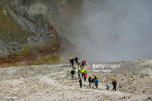 Tourists walk beside the crater rim of White Island on July 9 2019 in Whakatane New Zealand