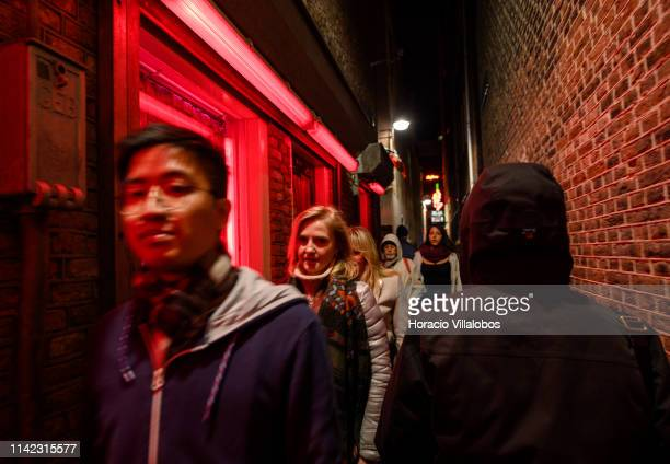 Tourists walk by glass doors in the Red Light District on April 12 2019 in Amsterdam The Netherlands Amsterdam is famous for its window prostitution...